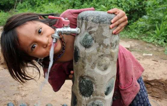 Young girl from third world country drinking from water fountain.