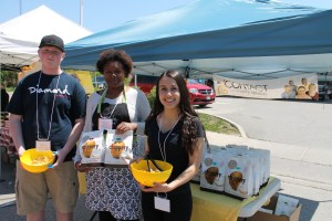 Carol Maitland (centre), fundraising and communications coordinator for CONTACT Community Services, selling Chippery Potato Chips for $5 bag at the Honey & Garden Festival. The chips are made right here in Alliston, from potatoes containing no GMO's. Proceeds from the sale of the chips will benefit CONTACT, a registered non-profit charity which provides a range of free services to the residents of South Simcoe. For ways that you can contribute, e-mail carol@contactsouthsimcoe.ca, or call 705 435-4900.