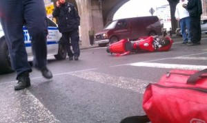Photo of crashed motorcycle on the street after being cut off by a car