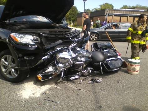 Who's fault is it when a car makes a left turn? This photo shows an SUV that made a left turn into a Harley-Davidson motorcycle. It was the car's fault.