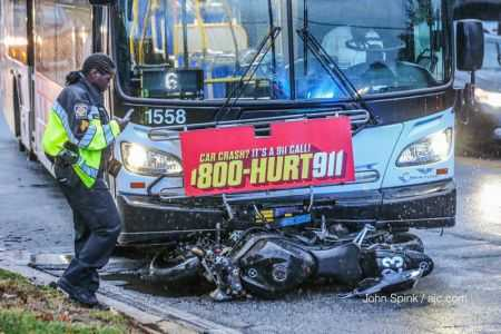 Why didn't the driver see the motorcycle? This bus driver caused a motorcycle accident with the motorcycle under the bus and the 1-800-HURT-911 sign hanging over the motorcycle