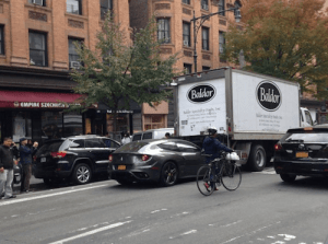 This image shows a truck and car double parking in NYC
