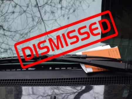"This image is a NYC parking ticket under wiper of car with word, ""Dismissed"" showing above the parking ticket"