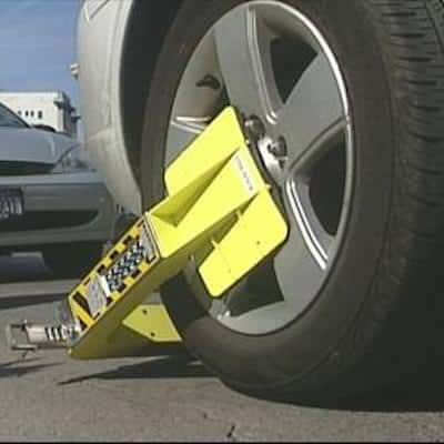 This image is a yellow boot attached to the wheel of a scofflaw's car