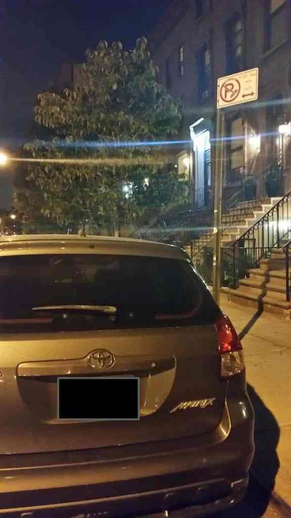 This image shows a car parked legally and a parking sign
