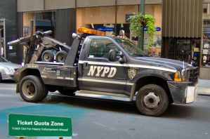 This image is a police tow truck with a parking ticket quota sign below