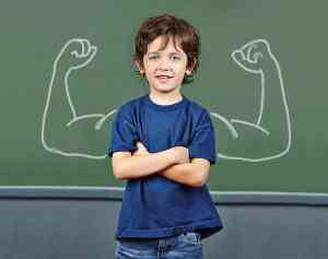 Strong child with muscles drawn on chalkboard in elementary scho