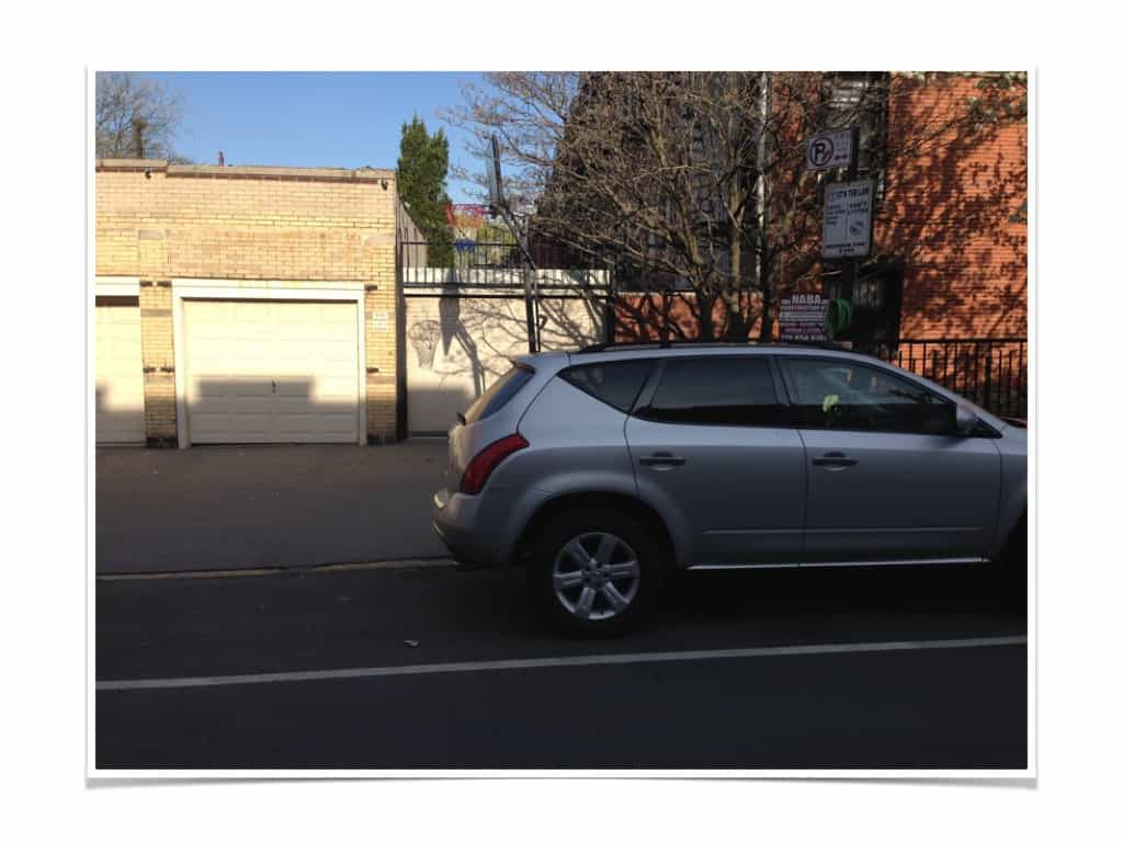 car parked in front of a NYC driveway