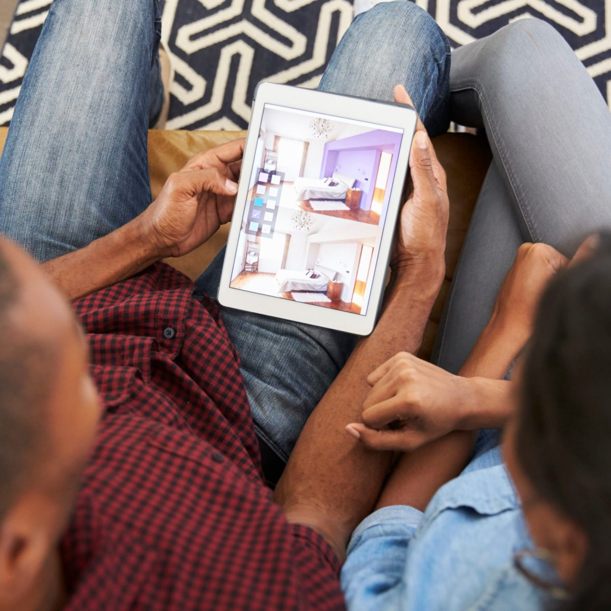 Couple Sitting On Sofa Looking At Home Improvement App