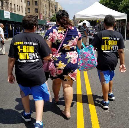 two boys wearing 1-800-HURT-911 T-shirts at Bronx street fair