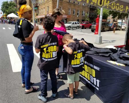 accident attorney Rob Plevy giving out free T-shirts to children at Bronx street fair