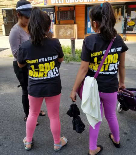 two girls wearing 1-800-HURT-911 T-shirts at Bronx street fair