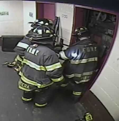 elevator doors being pried open by firefighters at an elevator accident