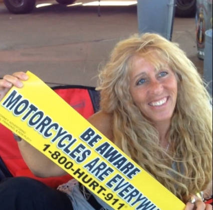 Donna holding a BE AWARE MOTORCYCLES ARE EVERYWHERE® car sign at the 1-800-HURT-911® New York Motorcycle Lawyers tent
