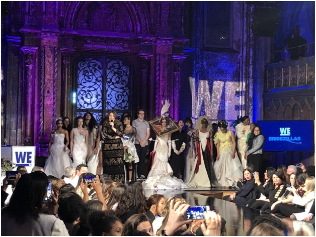 Host Michelle Collins recognizes the designers on stage competing