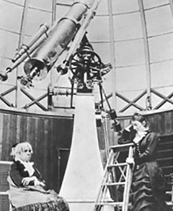 """Maria Mitchell (seated) in her observatory at Vassar College, circa 1877. Photo from """"Heroes of Progress: Stories of Successful Americans"""" by Eva March Tappan, 1921."""
