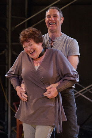 """Nigel Gore, his belt wrapped around Tina Packer, about to perform a scene from """"The Taming of the Shrew"""""""
