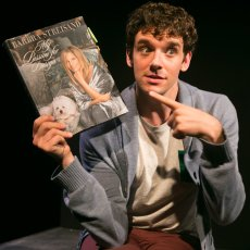 Urie pointing to Streisand's coffee table book