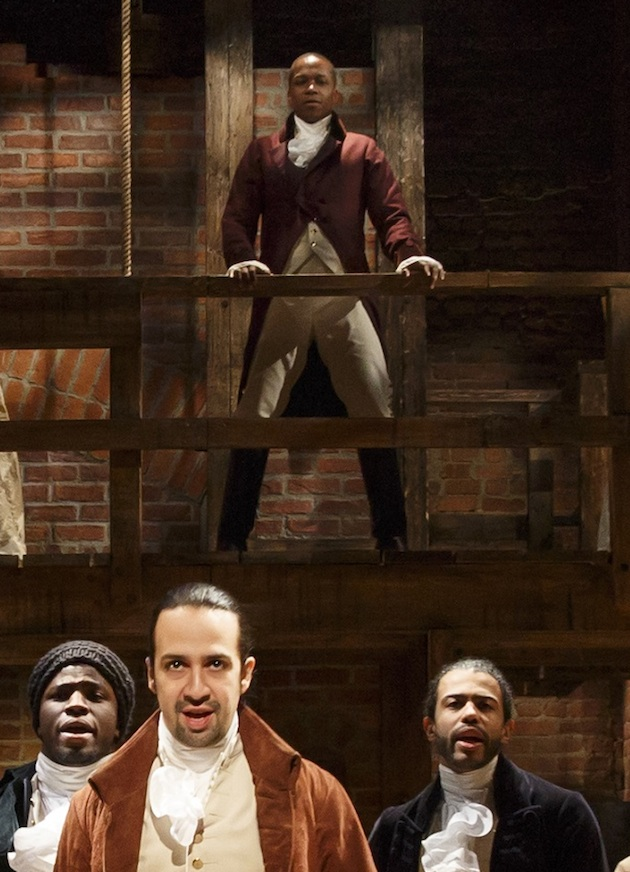 Leslie Odom Jr as Aaron Burr on ramp above Lin-Manuel Miranda as Hamilton., flanked by Okieriete Onaodowan as James Madison and Daveed Diggs as Thomas Jefferson.