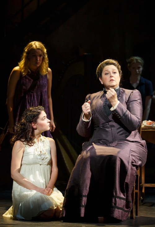 """Katie Boeck and Sandra Mae Frank as Wendla and her voice, with Camryn Manhein as their mother, Frau Bergman. Wendla and her mother, Frau Bergman: Wendla insists that her mother finally explain the birds and the bees to her. Pressured by this persistence, Wendla's mother agrees to do so, but stumbles and stutters, and finally says: For a woman to bear a child, she must love her husband, only him, """"with her whole….heart."""" End of lesson. This gets an enormous laugh, and not just because she's chickened out. Camryn Manheim, who plays the mother (the one stand-out adult performance), is both speaking and signing her part. After she says """"whole,"""" she puts her hands together near her waist to form the ASL sign for """"vagina,"""" but then quickly moves it up to her heart and says the word """"heart"""" instead. (The reason why everybody in the audience can get this joke, even those who know not a single ASL sign, is that the sign for vagina – the outstretched thumb and forefinger of both hands touching one another — looks unmistakably like a vagina. That took forever just now to describe in print, but it happens in a moment on stage.)"""
