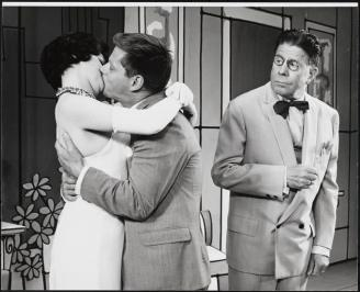 Annie Scott as Rosemary Pillkington kisses Robert Morse as J. Pierrepont Finch, as Rudy Vallee as the boss looks on shocked in How to Succeed in Business without really Trying 1961