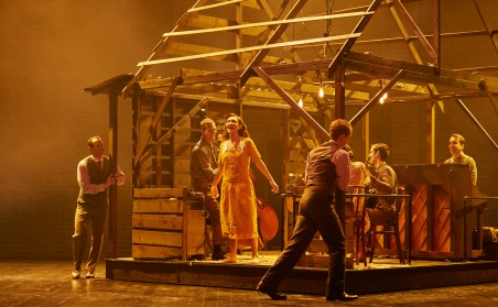 The performers in a centerpiece of the set that doubles as a log cabin, a bandshell for the musicians, and a romantic gazebo