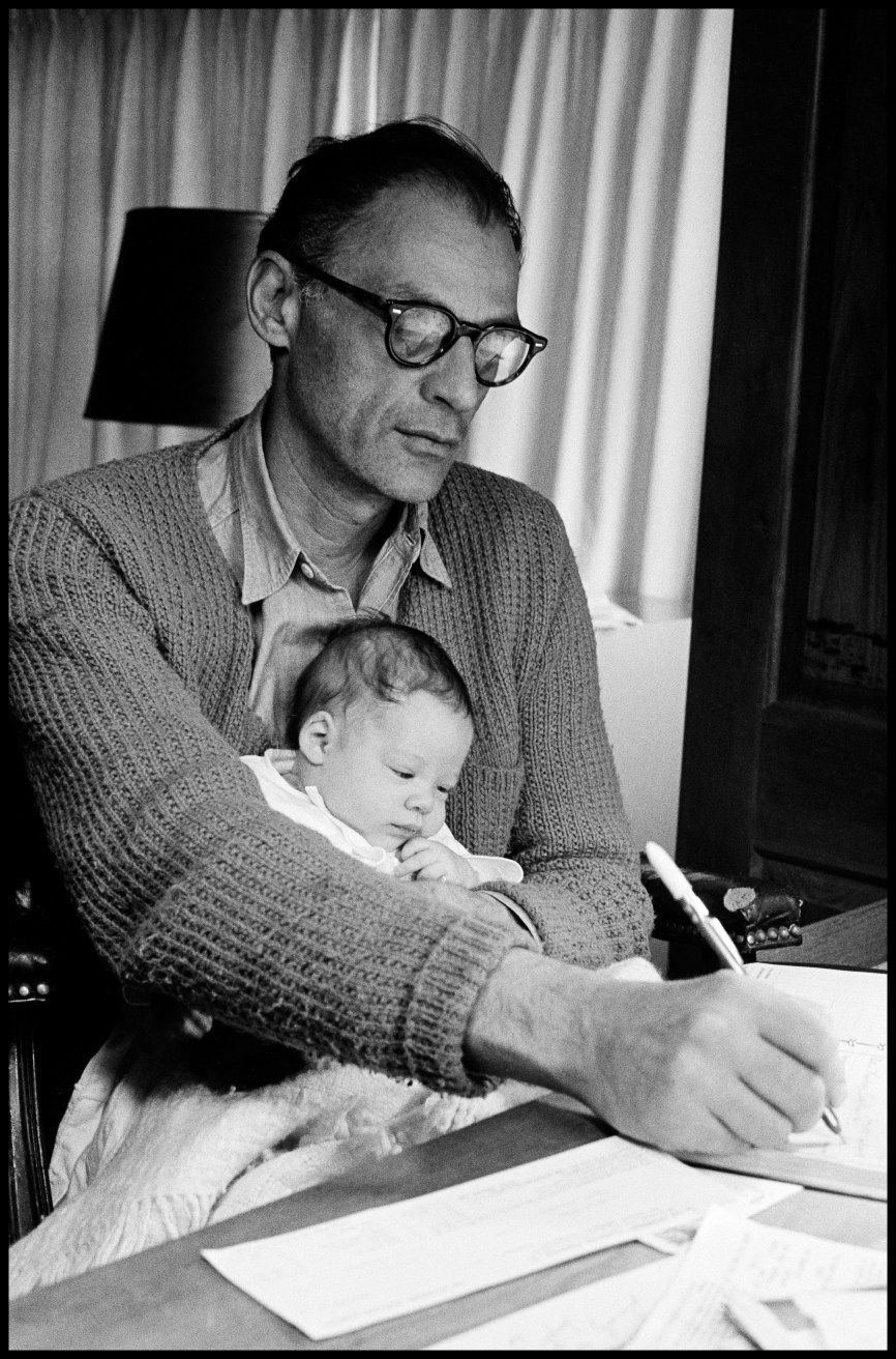 USA. Roxbury, CT. 1962. Playwright Arthur Miller at his desk with daughter Rebecca.