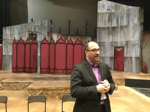 """Brian Isaac Phillips, CSC's producing artistic director in front of the set for the current production of """"Othello."""""""
