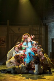 Molly Gordon as Alice surrounded by cast