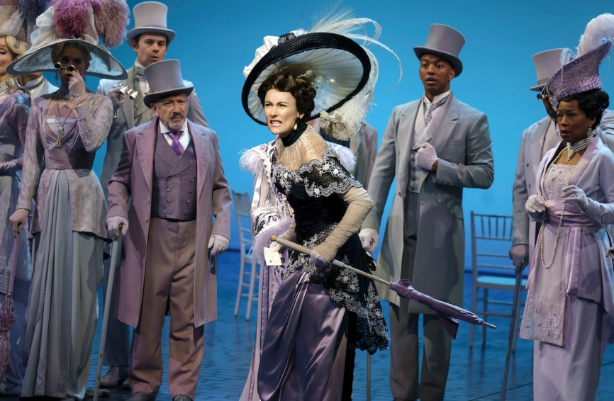 Laura Benanti as Eliza Doolittle and Christian Dante White as Freddy to her left, with Allan Corduner as Colonel Pickering to her right. At the Ascot races.