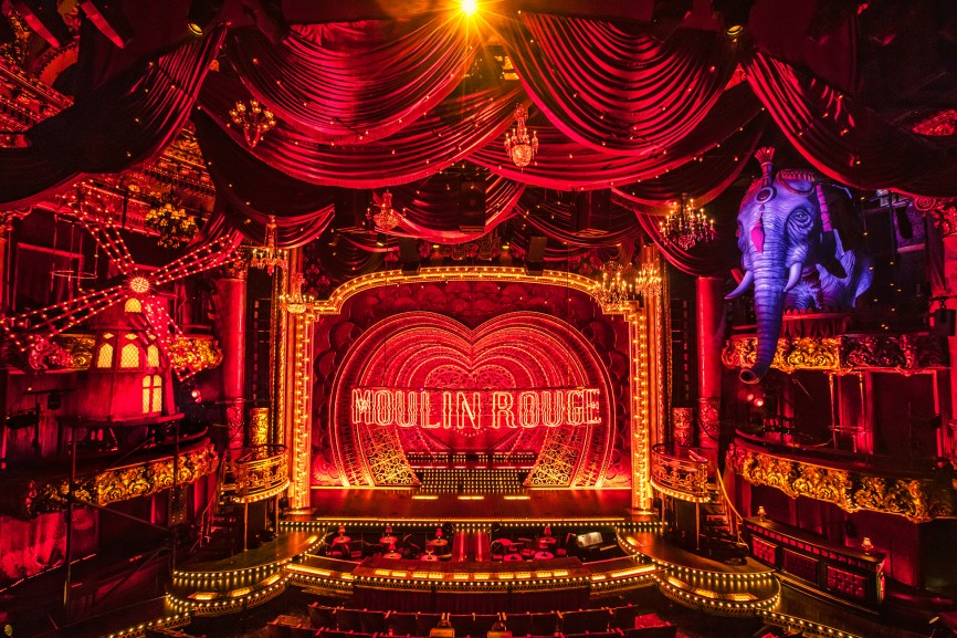 """Moulin Rouge"" was thrilling from the moment you entered the theater… until about ten minutes after it began. That's because the brightest star in this stage adaptation of Baz Luhrmann's 2001 movie musical is designer Derek McLane's set. Before we even take our seats, it envelopes us in love, or at least in lots of red – a huge red neon ""Moulin Rouge"" sign above red lights in the shape of a half a dozen hearts nestled lovingly within each other, a full-sized, red windmill full of lights perched on the box seats above us to our left, a life-sized elephant (which, for variety, is purple) in the box seats to our right…"