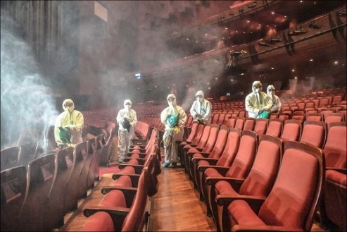 Workers in protective gear disinfecting an empty theater in Seoul, Korea. Theaters have been shut down in several world cities because of COVID-19. Will this happen in New York?