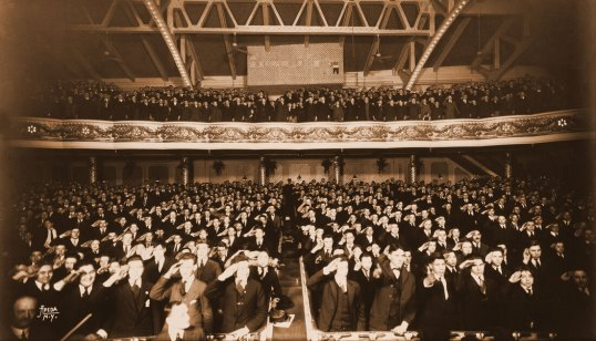 """Audience of schoolboys, Winter Garden Theatre, 1916. The original design for the Winter Garden interior was meant to evoke an actual winter garden, hence the exposed cast iron ceiling, the trellis effect on the rear wall of the orchestra, and the garlands and floral motifs throughout. Most noteworthy was the runway that extended down the center aisle. This was dubbed the """"Bridge of Thighs"""" in honor of the scantily clad chorus girls that paraded up and down it. Between 1922 and 1923, the Shuberts asked Herbert Krapp to remodel the theatre using his more traditional Adamesque style."""