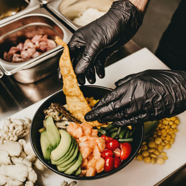 Chef wearing protective equipment prepares a gorgeous meal.