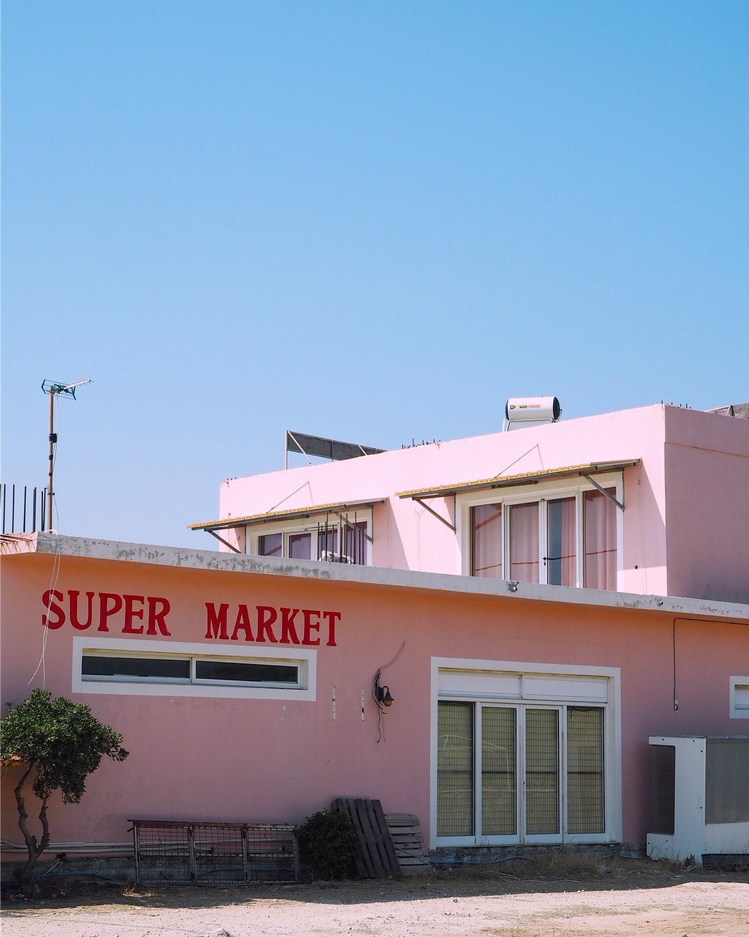 pink supermarket against blue sky