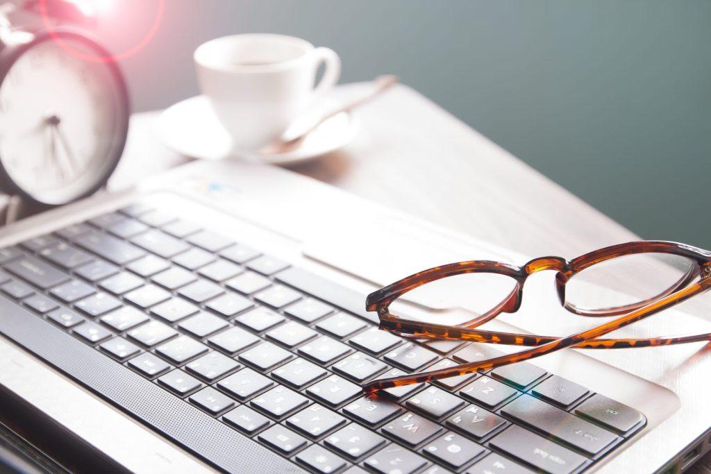 Teksty SEO. Okulary leżące na klawiaturze laptopa.