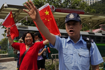 A police officer tries to keep the pro-China supporters in order at the Peak in Hong Kong Sunday, Sept. 29, 2019. Hundreds of pro-Beijing supporters sang Chinese national anthem and waved red flags ahead of China's National Day, in a counter to…