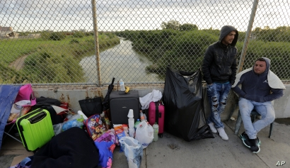 FILE - Yenly Morales, left, and Yenly Herrera, right, immigrants from Cuba seeking asylum in the United States, wait on the Brownsville and Matamoros International Bridge in Matamoros, Mexico, Nov. 2, 2018.