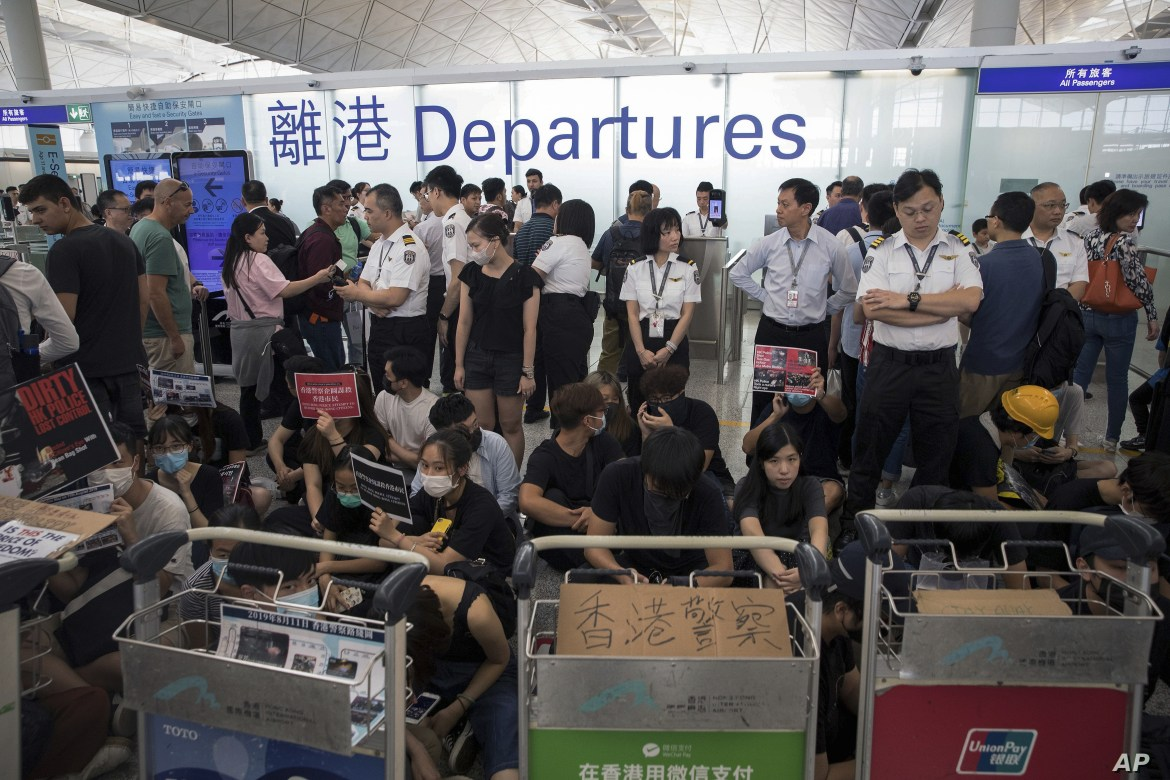 Airport security personnel stand guard as travelers walk past protesters holding a sit-in rally at the departure gate of the Hong Kong International Airport in Hong Kong, Aug. 13, 2019.
