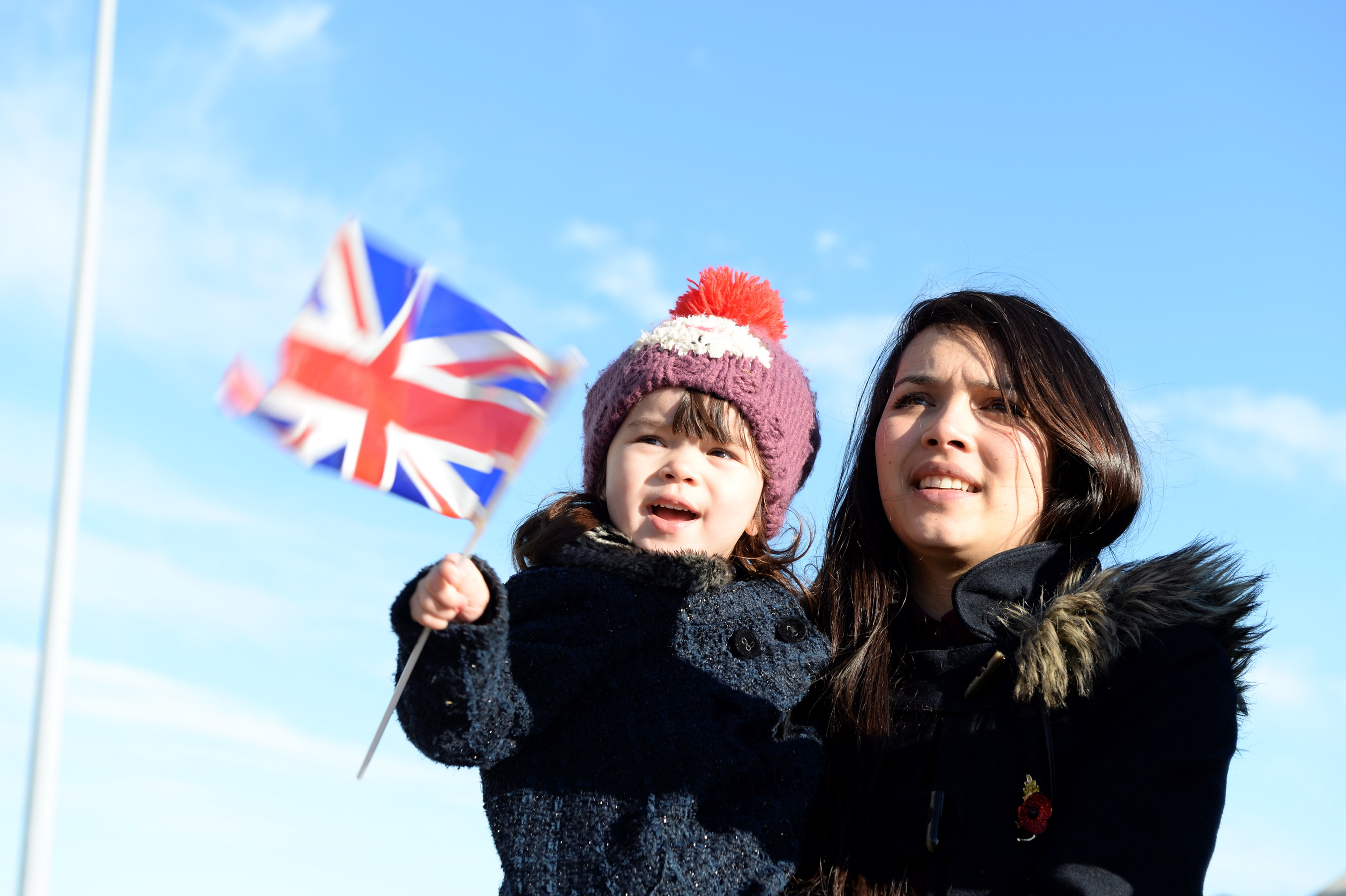 Mother and daughter waiting for ship to return, daughter waving a flag.