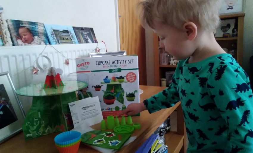 Boy playing with cupcake activity set.