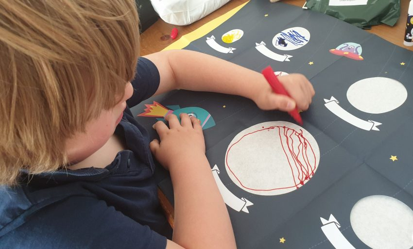 Boy drawing a planet and colouring it in.
