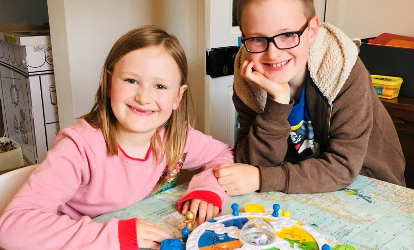 Two children smiling into the camera while playing board game.