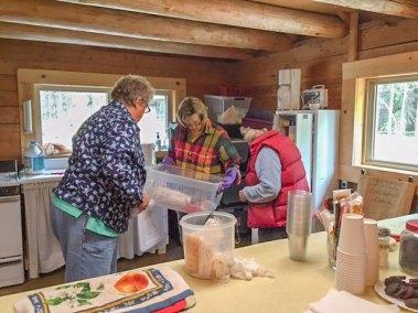 Karen, Chris, and Donna organize the kitchen