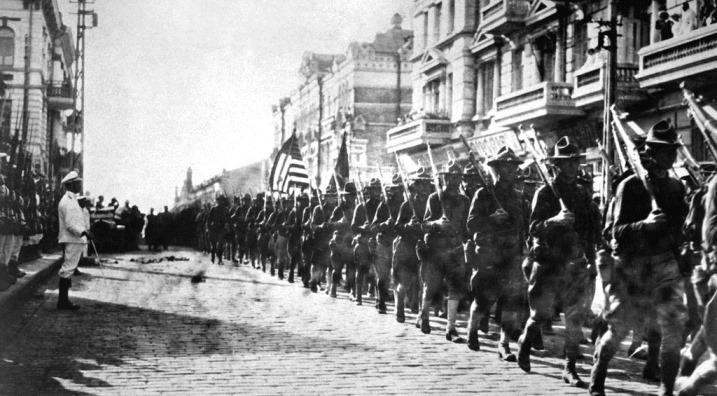 American troops in Vladivostok parading before the building occupied by the staff of the Czecho-Slovaks.  Japanese marines are standing at attention as they march by.  Siberia, August 1918.  Underwood and Underwood.  (War Dept.) Exact Date Shot Unknown NARA FILE #:  165-WW-558C-4 WAR & CONFLICT BOOK #:  354