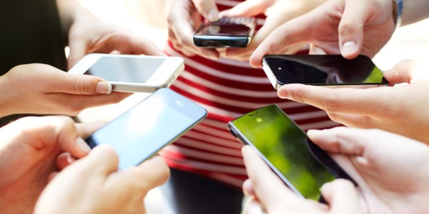 Close up of friends with circle of smart phones