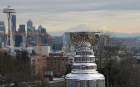 Stanley Cup em primeiro plano, e a cidade de Seattle atrás