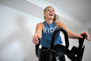 Meagan Ferns smiling and riding an indoor cycle