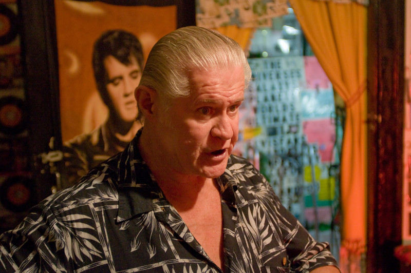 Paul McLeod, framed by Elvis's image and a sheet of hundreds out of the tens of thousands of Elvis-related photographs he has collected
