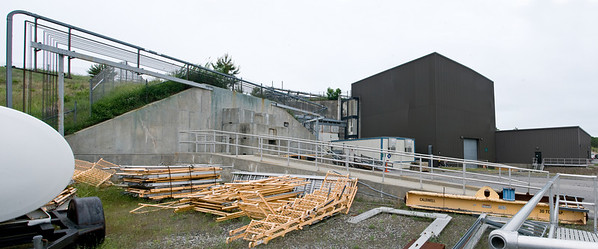 A panoramic view of the PHENIX detectors building and counting house. To the left, an entrance to RHICs particle beam ring is visible. When access is required, the enormous concrete slabs that block the entrance are removed with a crane to expose the route into the tunnel.